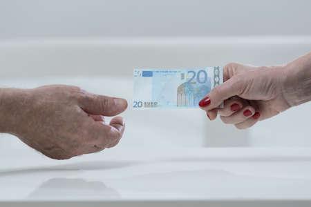 dinero euros: Una más vieja mujer entrega un billete en euros al anciano