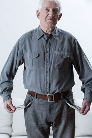 Sad elderly poor man standing with empty pockets