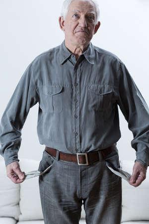 Triest bejaarde arme man met lege zakken Stockfoto