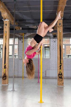 cabeza abajo: Mujer deportiva posando boca abajo en el pilón