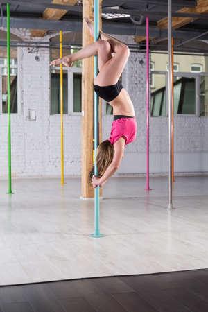 Young beauty pole dancer doing advanced figure