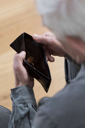 sadly: Older man looking sadly at an empty wallet
