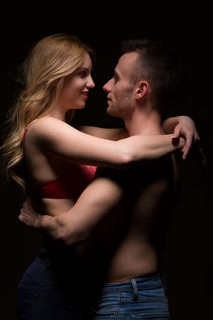 intimate sex: Couple of lovers posing on black background
