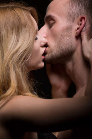 young couple sex: Portrait of sensual couple kissing - black backround