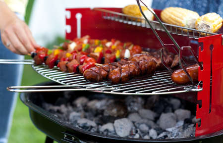frazzled: Sausages, shiskebabs and corns lying on the grill Stock Photo