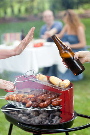 frazzled: Person refusing beer on party in garden Stock Photo