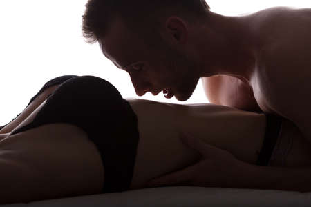 romance sex: Man kissing female stomach during passionate foreplay Stock Photo