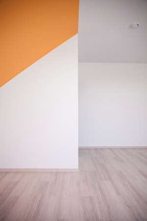 Unfurnished bedroom with white and orange walls and wooden floor
