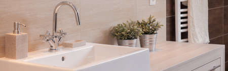 warm color: Close-up of clean sink with floral decorations in modern bathroom