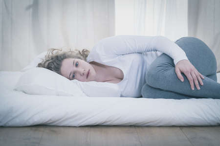 despairing: Depressed young woman lying in curled position Stock Photo