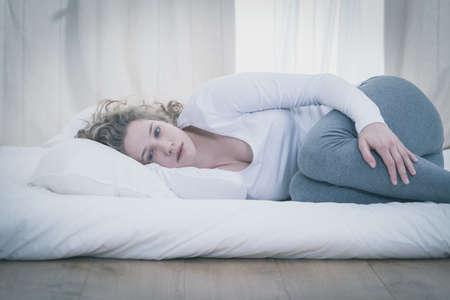 cama: Mujer joven deprimida acostada en posición fetal Foto de archivo