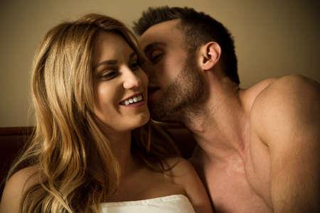 Hermoso hombre coqueteando con la mujer sexy en la cama