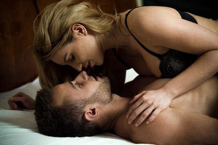 erotico: Donna seducente uomo disteso su di lui in lingerie sexy