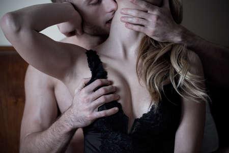 Человек ласкает шею и грудь женщины в постели Фото со стока
