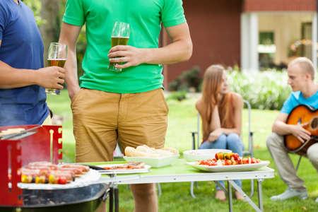 grupo de hombres: Los hombres jóvenes que hablan en el jardín con la cerveza en sus manos