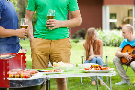 party table: Young men talking in the garden with beer on their hands Stock Photo