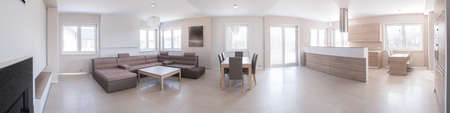 Panoramic photo of modern living room connected with wooden kitchen