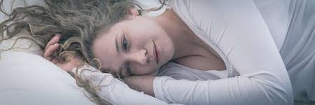 mujer en la cama: Triste niña de belleza casi llorando en la cama
