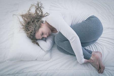 mujer triste: Mujer joven desesperada acurrucada en la cama Foto de archivo