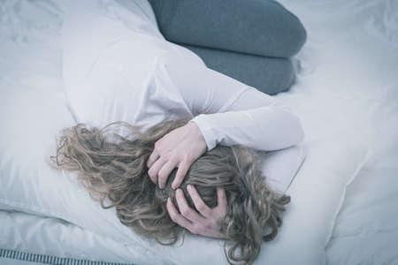 persona triste: Mujer joven preocupada acurrucada en la cama Foto de archivo