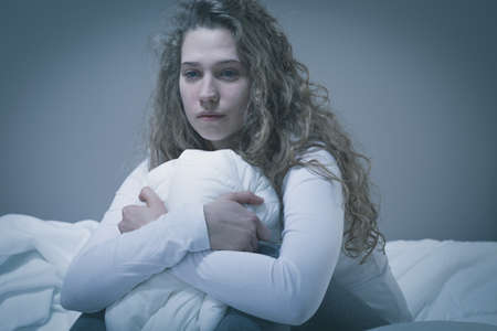 Woman with deep depression sitting in bed Stock Photo