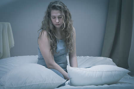 Girl with serious depression sitting in bed photo