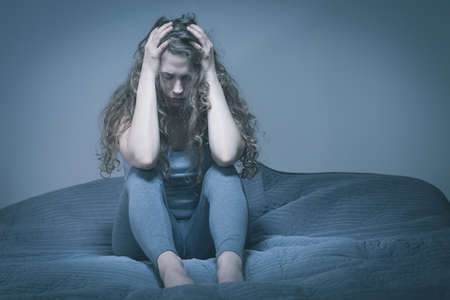 desperate: Desperate young woman sitting alone in gray room Stock Photo