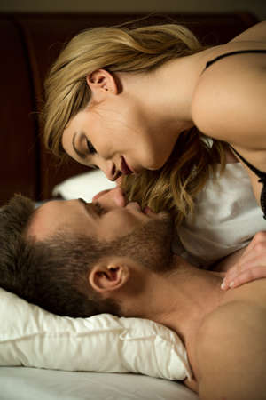 intimate sex: Foreplay young pair of lovers in bed Stock Photo