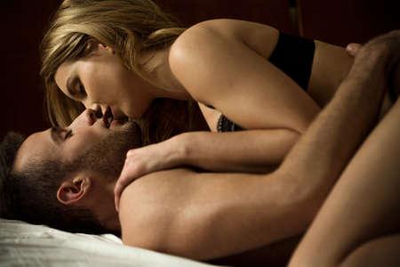 sexo: Joven pareja besándose apasionadamente mientras está acostado en la cama
