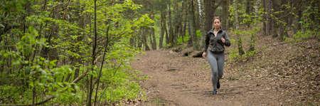 runner: Panorama of sportswoman running throught the park