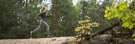 森の中を実行している女性トレーニング トレイル 写真素材