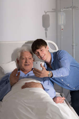 man in hospital bed: Older sick man and his grandson and video conference online Stock Photo