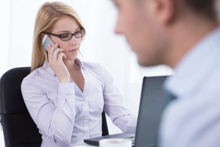 transact: Attractive corporate woman talking on the phone with client Stock Photo