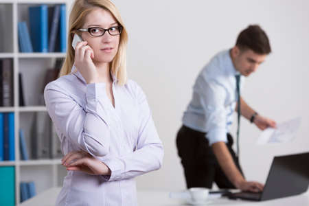 transact: Pretty young female boss talking on the phone with client Stock Photo