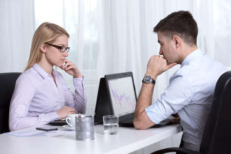 employee: Two focused employees working on laptops at office