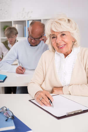 old women: Elder student with empty paper during exam