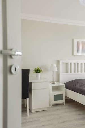Vertical view of open door to cozy bedroom photo