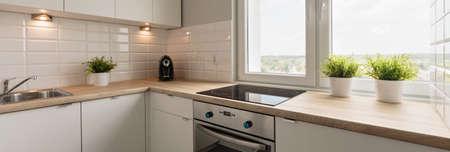 木製の調理台と居心地の良いキッチンのホワイトの食器棚