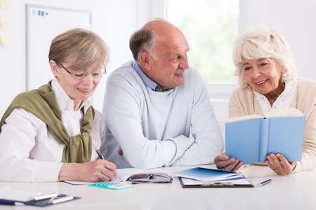 Lachend gelukkig gepensioneerden studeren aan de balie