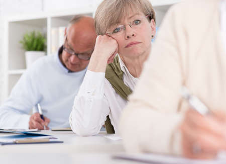 evening class: Image of worried woman writing difficult exam