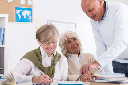 old office: Teacher helping elder student in the collage Stock Photo