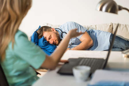 tired: Tired nurse is arguing with sleepy doctor Stock Photo