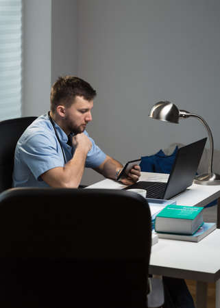 after hours: Busy doctor is working after hours in his lab Stock Photo