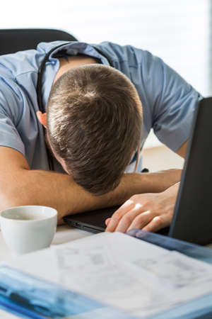 cheerless: Overworked doctor has enough of work, vertical photo Stock Photo