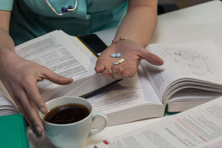 studing: Student of medicine takes pills for better concentration Stock Photo