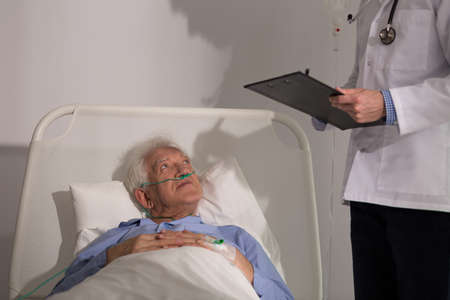 Professional doctor diagnosing his older sick patient Stock Photo