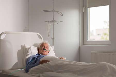 hombre solo: Enfermo terminal triste sola en cama de hospital Foto de archivo