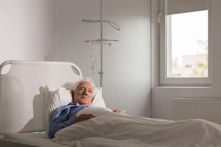 older men: Lonely sad terminally ill patient in hospital bed