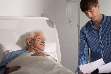 Young grandson reading the documents to his sick grandfather Stock Photo - 41084067
