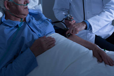aide a la personne: Doctor measuring aged mans blood pressure